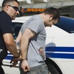 police officer arresting drug dealer with car in the background