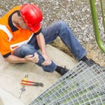 High angle view of mid adult worker suffering from leg pain by storage tank steps in park